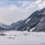Winter mountain landscape in the Alps. The valley, meadow, trees and mountains covered with snow.
